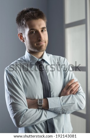 Confident businessman with arms crossed smiling at camera.