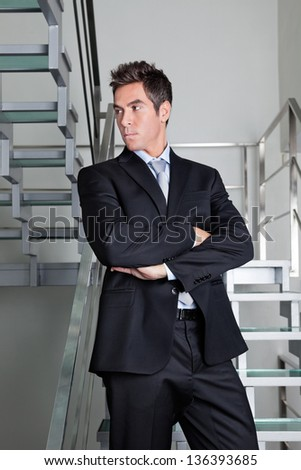 Confident businessman with arms crossed standing on stairs - stock photo