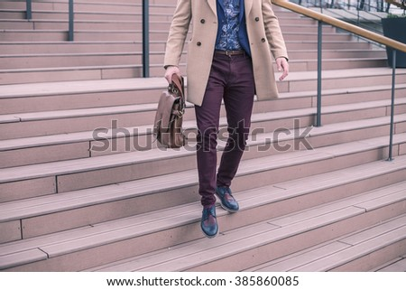 Confident businessman with bag walking the stairs