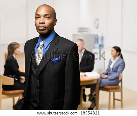 Confident businessman with co-workers in background - stock photo