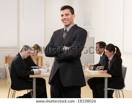 Confident businessman with co-workers meeting in conference room behind him - stock photo