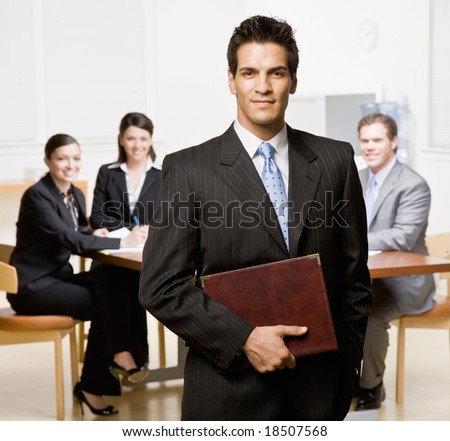 Confident businessman with notebook and co-workers in conference room - stock photo