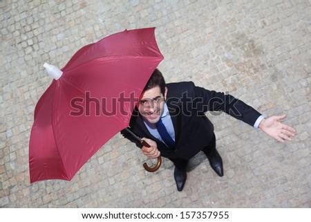 Confident businessman with umbrella checking if it's raining - stock photo