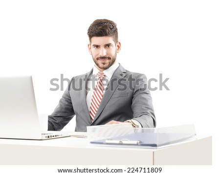 Confident businessman working on laptop, while sitting against white background.