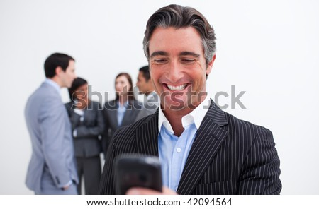 Confident businessman writing a text with a mobile phone in the office - stock photo