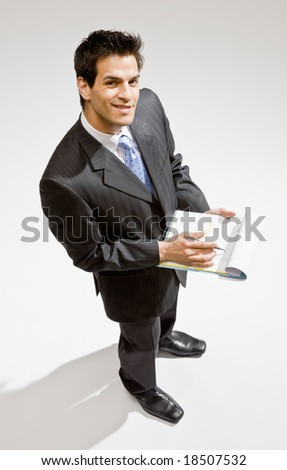 Confident businessman writing on clipboard - stock photo
