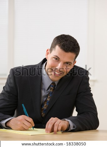 Confident businessman writing on legal pad taking notes - stock photo