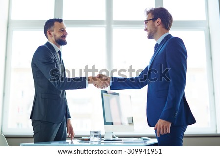 Confident businessmen handshaking over workplace in office - stock photo
