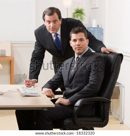 Confident businessmen looking serious at desk in office - stock photo