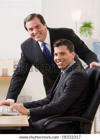 Confident businessmen smiling at desk in office - stock photo
