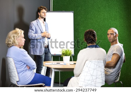 Confident businesspeople discussing during presentation at office lobby