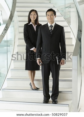 Confident Businesspeople standing on staircase - stock photo