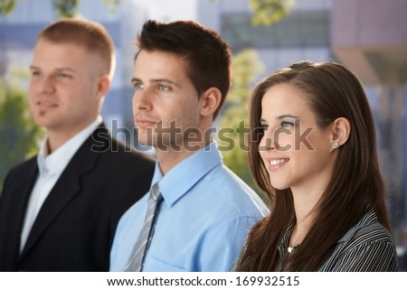 Confident businessteam standing outside of office building, smiling. - stock photo