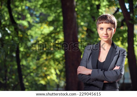 Confident businesswoman. Attractive young caucasian businesswoman in suit keeping arms crossed and looking at camera outdoors - stock photo