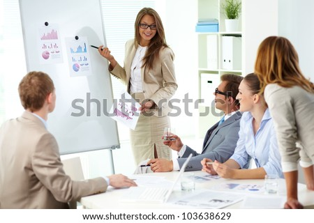 Confident businesswoman commenting marketing results to colleagues at meeting - stock photo