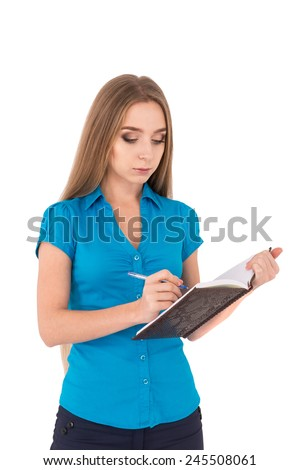 Confident businesswoman. Confident young business woman writing something in her note pad while standing isolated on white - stock photo
