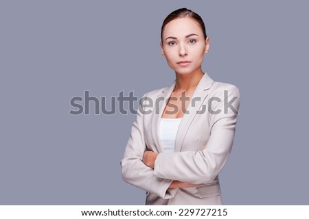 Confident businesswoman. Confident young businesswoman keeping arms crossed while standing against grey background - stock photo
