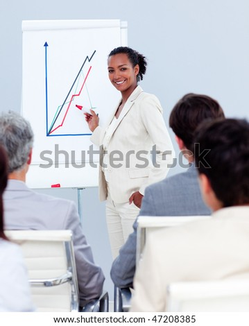 Confident businesswoman doing a presentation to her team - stock photo
