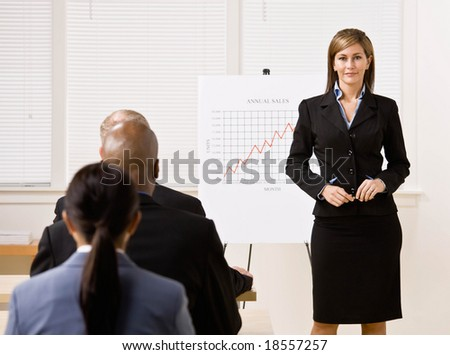 Confident businesswoman explaining financial analysis chart to co-workers - stock photo