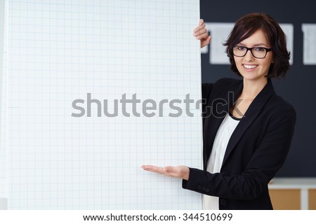 Confident businesswoman giving a presentation gesturing with her hand towards a blank sheet of graph paper on a flip chart with a smile, copyspace for your text or diagram - stock photo