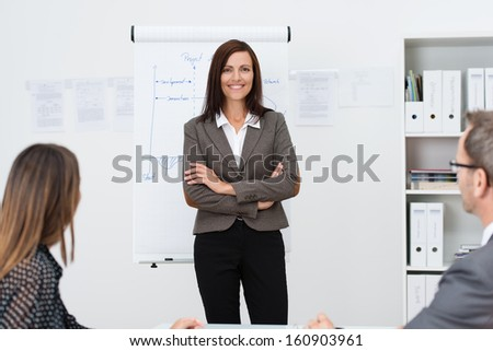 Confident businesswoman giving a presentation to her colleagues standing facing them in front of a with her arms folded - stock photo