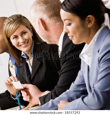 Confident businesswoman handing co-worker business card in meeting - stock photo