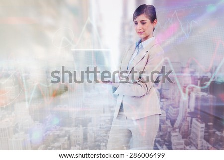 Confident businesswoman holding laptop against high angle view of city - stock photo