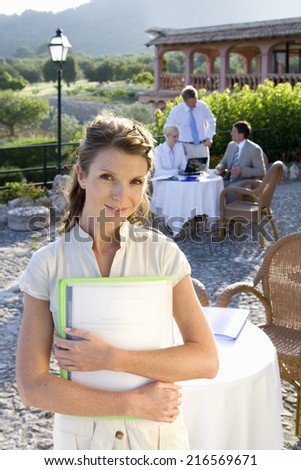 Confident businesswoman holding paperwork at caf�½ with coworkers in background - stock photo