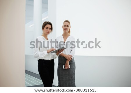 Confident businesswoman holding touch pad while standing with her secretary in modern office interior during break between conference, female using digital tablet for discuss work issues with partner - stock photo