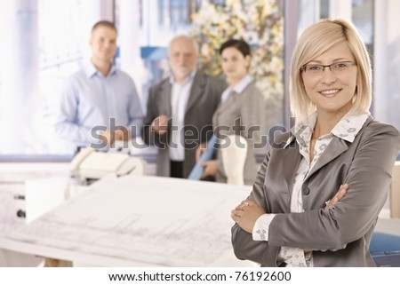 Confident businesswoman in focus smiling with arms crossed with team in background of office.? - stock photo