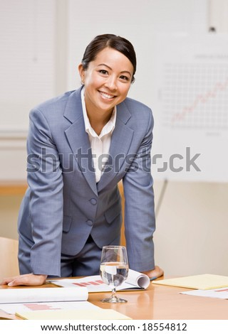 Confident businesswoman leaning on table in conference room - stock photo