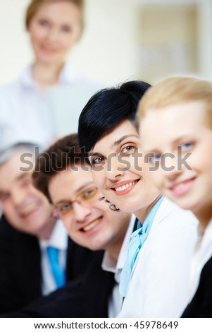 Confident businesswoman looking at camera among her colleagues