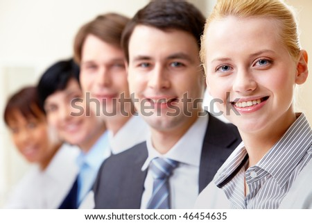 Confident businesswoman looking at camera with colleagues on background