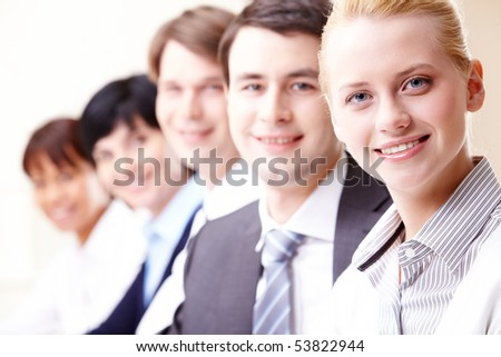 Confident businesswoman looking at camera with colleagues on background - stock photo