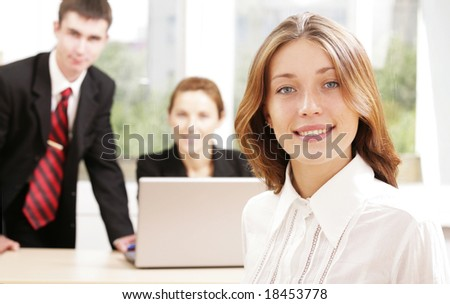 Confident businesswoman looking at camera with working partners at background