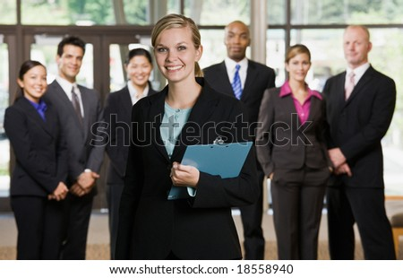 Confident businesswoman posing in front of co-workers - stock photo