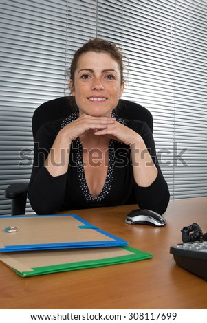 Confident businesswoman posing on a table - stock photo