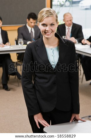 Confident businesswoman preparing for presentation on laptop in conference room - stock photo