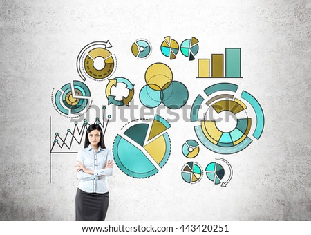 Confident businesswoman standing against concrete wall with business pie charts - stock photo
