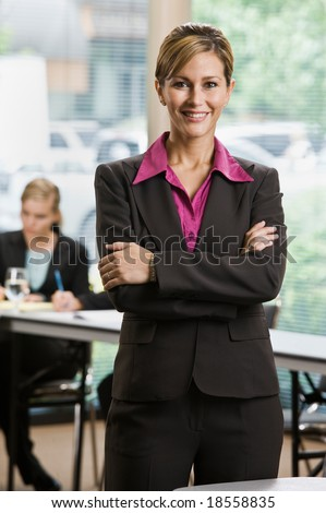 Confident businesswoman standing in front of co-workers in conference room - stock photo