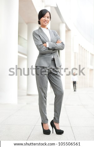 Confident businesswoman standing outside and looking at camera - stock photo