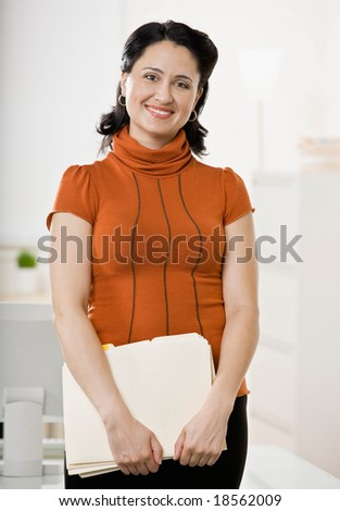 Confident businesswoman standing with file folders - stock photo