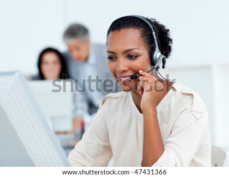 Confident businesswoman talking on headset at work - stock photo