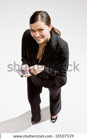 Confident businesswoman using electronic organizer to schedule appointment - stock photo
