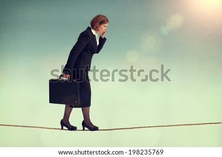 confident businesswoman walking a tightrope or highwire multitasking  - stock photo
