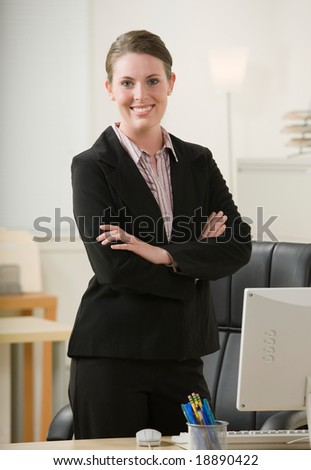 Confident businesswoman with arms crossed at desk - stock photo
