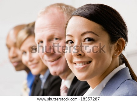 Confident businesswoman with co-workers - stock photo