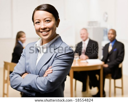 Confident businesswoman with co-workers in background - stock photo