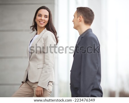 Confident businesswoman with coworker in front of office building - stock photo