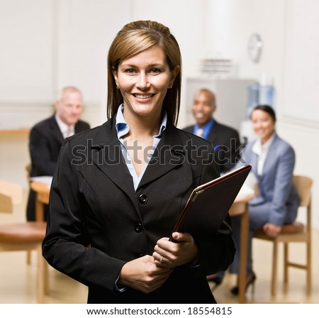 Confident businesswoman with notebook and co-workers in background - stock photo